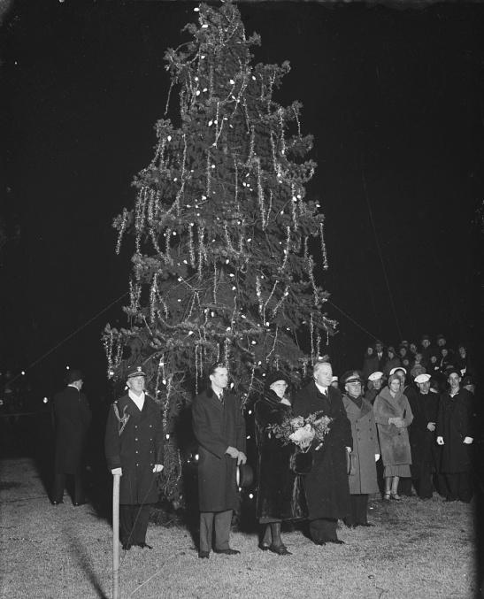 "President lights Christmas tree. President Hoover pressed the button which lighted Washington's community Christmas tree just before he began his brief ""Merry Christmas"" radio address to Americans from coast to coast. Mrs. Hoover accompanied the President to the impressive Christmas program, which included music by the U.S. Marine band. 12/24/30, photo from the Library of Congress."